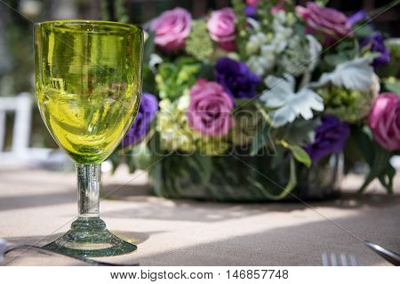 Formal table setting for a wedding with floral centerpiece and colorful green glasses