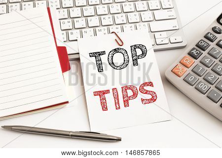 Word text Top tips on white paper card on office table / business concept