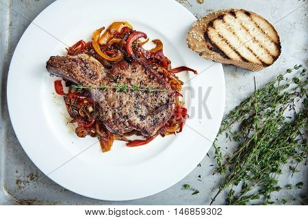 Delicious, juicy, fleshy, hot meat ribs on sauteed peppers and onions, decorated with a thyme sprig. Appetizing main dish on white plate with fried bun. Real mens food. Club Steak veal on the bone. poster