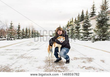 Man and dog in snow. Man Walking Dog Through Snowy Woodland