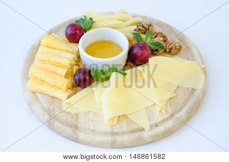 Cheese plate with cheeses Dorblu, Parmesan, Brie in serving on the table from an old tree close-up