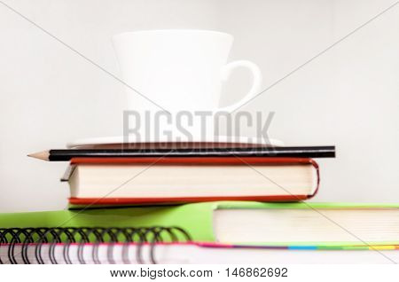 Pencil on notebook near pile of books on shelf with cup of coffee