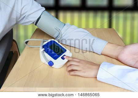 Concept of female press start button on blood pressure or sphygmomanometer in room background