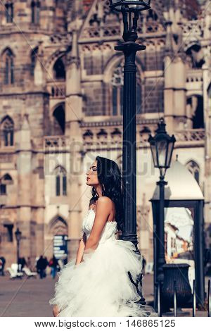 Beautiful bride pretty woman in elegant fashion white wedding dress poses on streetscape background