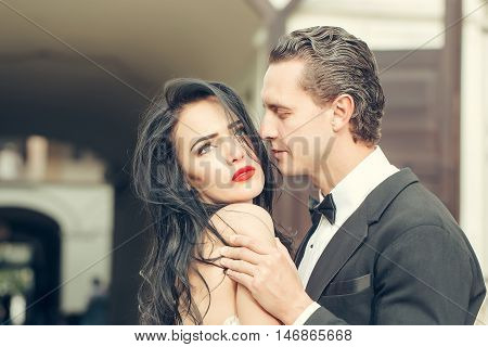 Handsome groom holds beautiful bride with passion sensual married couple outdoors on streetscape