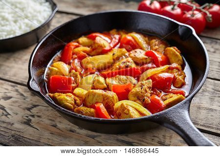 Chicken jalfrezi healthy traditional Indian culture restaurant meal curry spicy fried meat with chilli and vegetables, tomatoes, pepper, onion, asian food in cast iron pan on vintage table background