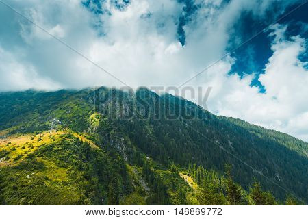 Wide angle photo of mountain peak covered by clouds. The photo is taken from Tranfagarasan road in fagaras mountains Romania.