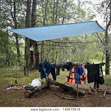 tourist camp in the woods, drying clothes in the rain