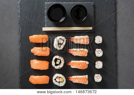 Sushi rolls set served on black stone slate. High angle view of sushi set nigiri and sushi rolls on black stone slate plate board. Japanese food served at restaurant with soy sauce and chopsticks.