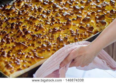 Hand touches tray with pastry. Lots of baked buns. Treats shaped as pine cones. Hot dough from the oven.