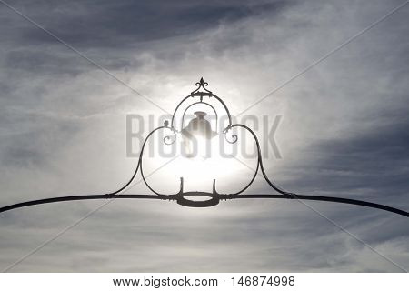 sun in the sky and a lamppost in front of it