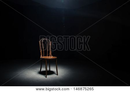 Lonely chair in the spot of light on black background at empty room