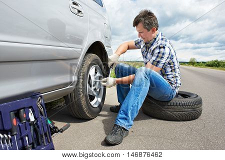 Man Changing Spare Tire Of Car