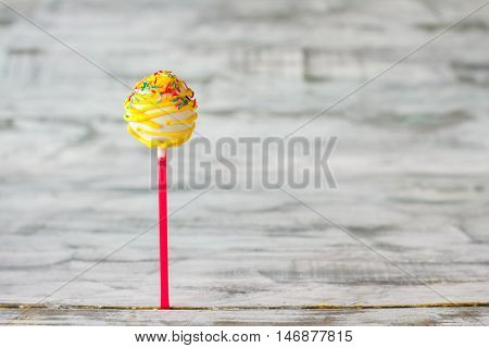 Yellow cake pop with sprinkles. Ball-shaped dessert on stick. Candy for the birthday kid. Fill the life with colors.