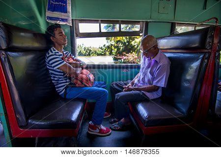 COLOMBO SRI LANKA - FEBRUARY 26 2016: Two unidentified passenger resting on a train near Colombo