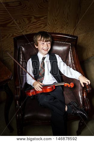 Freckled Red-hair Boy With Violin Sitting In The Arm-chair