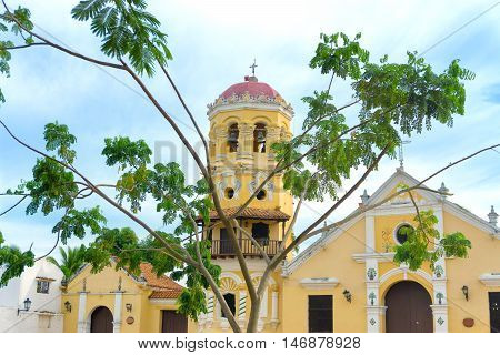 View of the yellow Santa Barbara church with a tree in front of it in Mompox Colombia