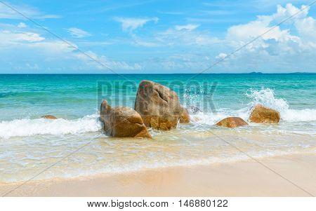 Clear azure sea crashing on rocks on tropical sandy beach