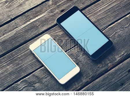 Two mockup smartphone with blank screen on wooden table