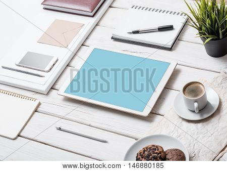 Mockup of a tablet pc on office desk, next to pens, pencils and so on. Clipping path for tablet included.