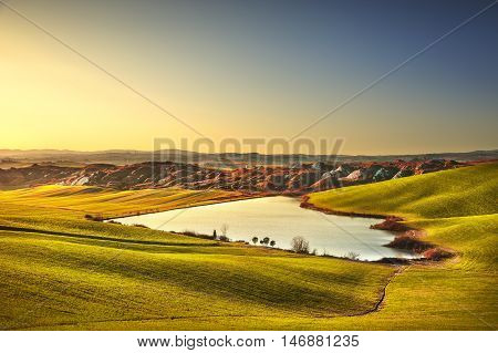 Tuscany Crete Senesi landscape near Siena Italy europe. Small lake green and yellow fields blue sky with clouds.