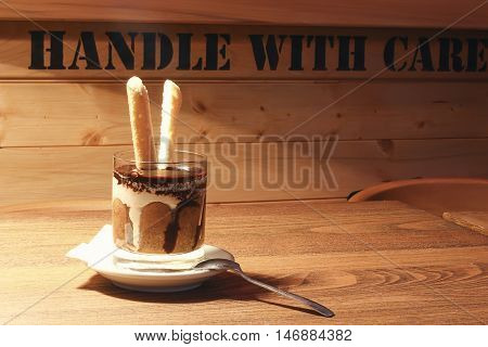 Tiramisu in a glass cup. Tiramisu in the glass on the wooden background.
