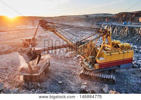 Mining. excavator loading granite or ore into dump truck