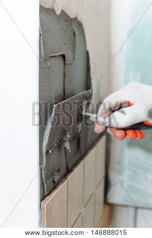 Worker instiling tiles on the wall in the kitchen. He put adhesive using a trowel.