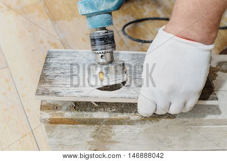 Tiler carves a hole in the tile using a diamond crown.
