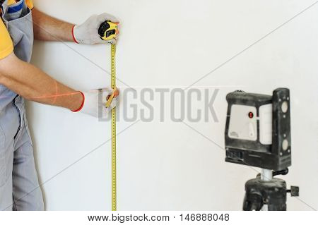 Worker making measurement using laser levels and measuring tape.