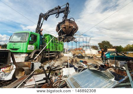 ZAGREB, CROATIA - OCTOBER 14, 2013: Truck driver using crane to collect garbage from recycling yard.