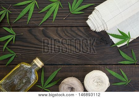 Leaves of cannabis, a bottle of hemp oil and tangles of thread on dark wooden surface. Hemp products. Agricultural technical culture. Top view