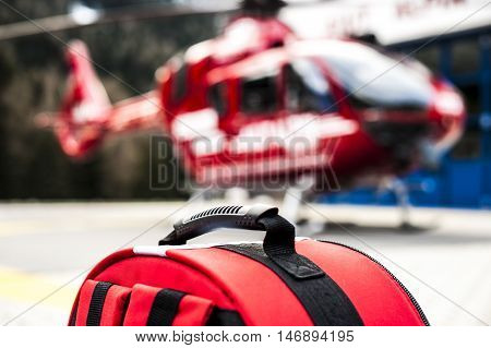 emergency rucksack with medical devices and a rescue helicopter
