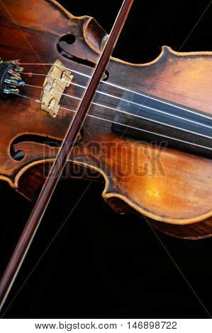 Old wooden violin and bow on isolated background. Violinist playing an Vintage fiddle. Beautiful classical music string instrument. An orchestral Symphony at the concert.