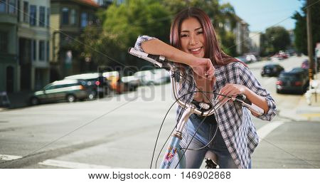 Chinese woman sitting on bike outdoors in San Francisco