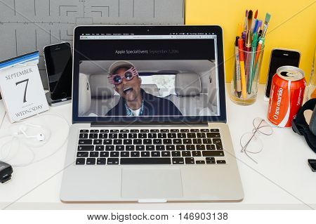 PARIS FRANCE - SEP 8 2016: Apple Computers website on MacBook Retina in room environment showcasing live coverage of Apple Keynote - CEO Tim Cook singing with James Corden and Pharrell Williams in a Carpool Karaoke type video