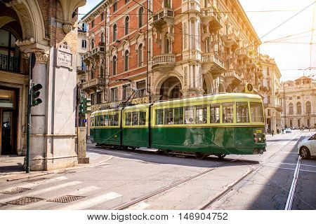 Turin, Italy - June 12, 2016: Street view with old green tram in the old city center of Turin in the morning in Piedmont region in Italy