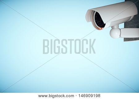 3D Rendering of a white CCTV security camera on light blue background with copy space