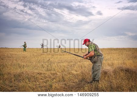 One hunter charges ammo and other hunters moving through the field