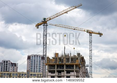 Construction of multi-storey buildings with Cranes. Workers work on building object.
