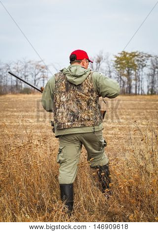 Hunter moving with shotgun looking for prey.
