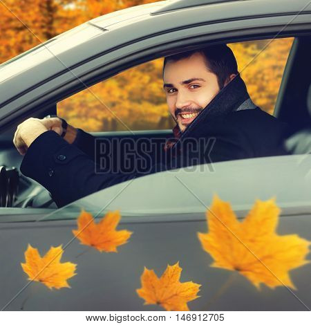 Transportation autumn and people concept - portrait happy smiling young man driver behind the wheel of his car