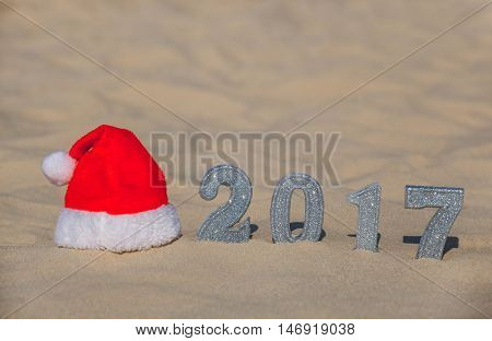 Red Santa's hat lies on the beach next to the sand are the numbers of the new year with silver sequins. New Year's holidays in the ocean or sea.