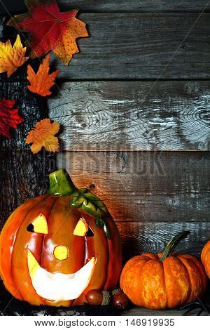 Lit Halloween Jack O Lantern With Pumpkin Corner Border Against A Rustic Old Wood Background