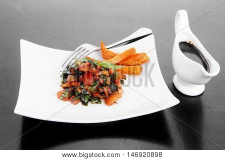 vegetable salad : cherry tomatoes and basil with sweet baked potato served on white plate with sauceboat full blask soy sauce on wood