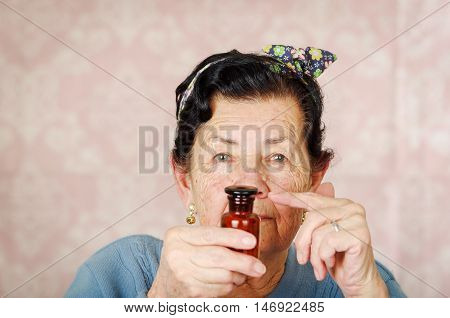 Older cool hispanic woman wearing blue sweater, flower pattern bow on head holding up a small red glass bottle for camera.
