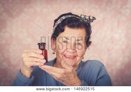 Older cool hispanic woman wearing blue sweater, flower pattern bow on head holding up a small red glass bottle and smiling to camera.