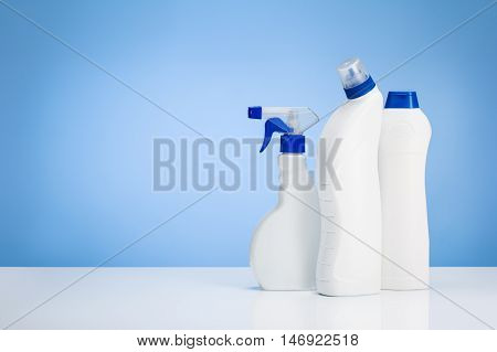House cleaning products on white table with blue gradient backdrop. Lots of copy space around objects.