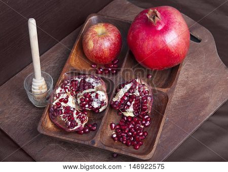 Ripe fall fruit on wooden board with honey stick