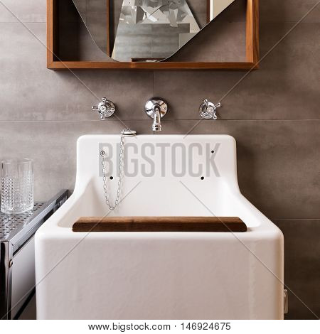 Close up of a vintage style bathroom sink with wood detail